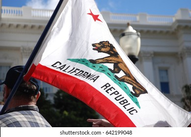 "SACRAMENTO, CALIFORNIA, USA - February 26, 2011: Labor union supporter carries California state flag at the California State Capitol during ""Rally to Save the American Dream"""