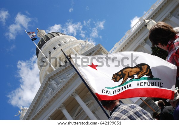 """SACRAMENTO, CALIFORNIA, USA - February 26, 2011: Labor union supporter carries California state flag at the California State Capitol during """"Rally to Save the American"""