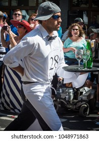 SACRAMENTO, CALIFORNIA/U.S.A. - JUNE 11, 2015: An unidentified man races toward the finish line trying not to spill a drop in the annual Bastille Day  Festival Waiters' Race.