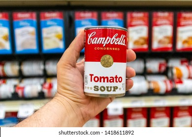 Sacramento, CA/USA 06/06/2019 Shoppers hand holding a tin can of Campbells Brand Tomato soup in a supermarket aisle