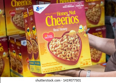 Sacramento, CA/USA 06/06/2019  Shoppers hand holding a family size package of Multi grain cheerios brand cereals in a supermarket aisle