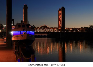 Sacramento, CA/USA 11/21/19 Blue hour shot of Capitol Hornblower tour boat docked in Old Sacramento preparing for a dinner cruise. Lighted Tower Bridge over the Sacramento River is in the background.