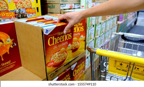 Sacramento, CA/USA 11/4/2019 Housewife buying a Box of Cheerios brand whole grain oats  cereals at a Supermarket aisle