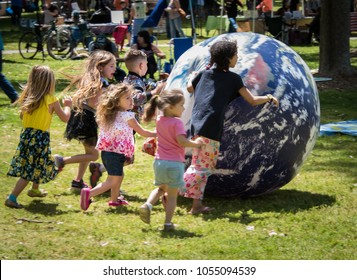 SACRAMENTO, CA/U.S.A. - APRIL 23, 2017: A group of unidentified children play with a large ball at the Earth Day celebration in Southside Park.