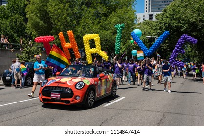 "SACRAMENTO, CA/U.S.A. - JUNE 10, 2018: Unidentified marchers carry rainbow ""Thrive"" balloons behind a Mini for Kaiser Permanente during the annual Pride parade and celebration for the LGBTQ community."