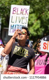 SACRAMENTO, CA/U.S.A. - JUNE 10, 2018: An unidentified transgender person takes a selfie in front of a Black Lives Matter sign during the annual Pride parade and celebration for the LGBTQ community.