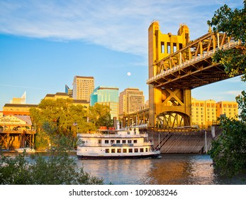 SACRAMENTO, CA/U.S.A. - JUNE 3, 2012: A view of Sacramento's skyline, including the vertical lift Tower Bridge and Hornblower river cruise boat.