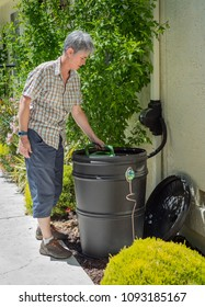 SACRAMENTO, CA/U.S.A. - MAY 12, 2018: Homeowner Chris Allan fills up her watering can from one of the rain catchment barrels she installed two years ago to help conserve water.