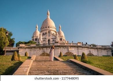 Sacre Coeur Cathedral in Montmartre, Paris, France, young woman on the stairs of Montmartre