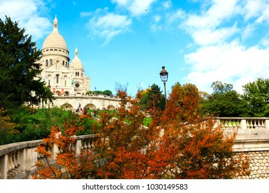 Sacre Coeur church at the top of Montmartre hill by autumn with bright blue sky on the backgorund.