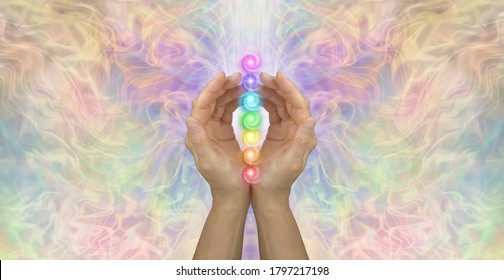 Sacred Chakras Healing Banner Concept - Female cupped hands with seven chakra vortexes in a stack between against an ethereal multicoloured energy background with copy space