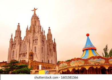 Sacred Heart of Jesus cathedral on Tibidabo hill with amusement park and carousel in Barcelona, Spain