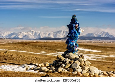 Sacred place with obo. Winter landscape of Mongolia. Lake Khubsugul and mountain in sunny day