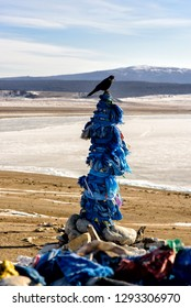 Sacred place with obo. Winter landscape of Mongolia. Lake Khubsugul and mountain in sunny day with crow
