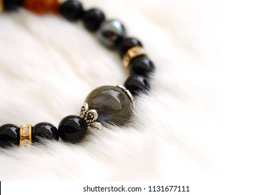 A sacred stone bracelet bead or lucky stone in black tone on white wool background. for good fortune and rich