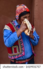 Sacred Valley, Cusco, Peru - Oct 13, 2018: An indigenous Quechua man blows on a Conch Shell