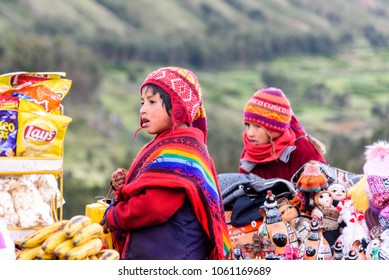 Sacred Valley, Peru - March 2018: Two young native Peruvian boys dressed in traditional clothes with Ponchis and hats at a market.