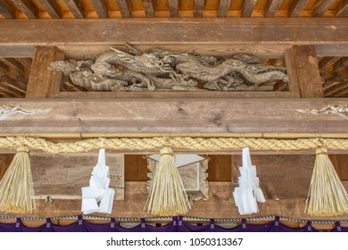 Sacred white zigzag strips of paper ('shime') hang from a sacred rice straw rope ('shimenawa') under a wooden dragon above the entrance to an old Shinto shrine in Japan.