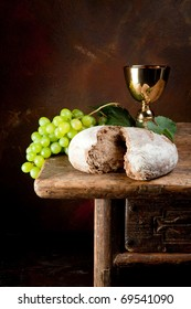 Sacred wine chalice with grapes and holy bread