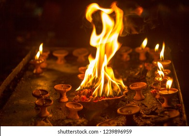 sacrificial fire in a bowl with flowers in the dark and small candles. burning candles. fire at night