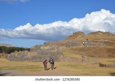 SACSAYHUAMAN / PERU, August 16, 2018: Tourists walk amid of the ruins of Sacsayhuaman