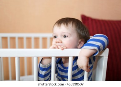 sad 1 year baby in white bed at home