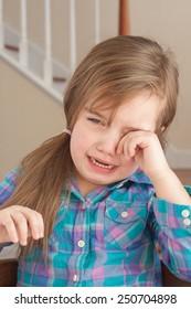 sad adorable little girl crying at home