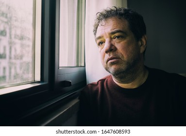 Sad adult man by the window in a dark room, bad mood concept
