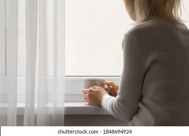 Sad adult woman sitting at window and holding mug in hands. Looking out from home. Thinking about life. Back view.