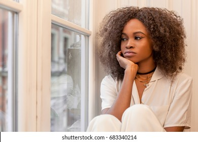 Sad african american girl sitting on the windowsill and looking out of the window.