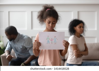 Sad african american school child girl holding family picture drawing feeling upset about parents divorce, innocent sensitive little kid suffer from trauma offended by fights conflicts shared custody