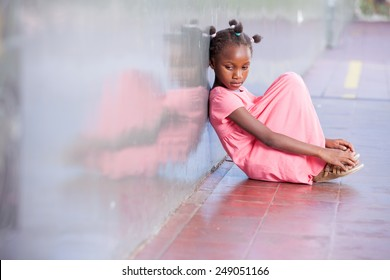 Sad african girl sitting and deeply thinking on the school floor.
