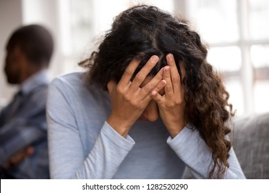 Sad african wife holding head in hands feeling desperate after fight with husband, upset frustrated black woman victim cry offended tired of quarreling, problems in bad couple relationships concept