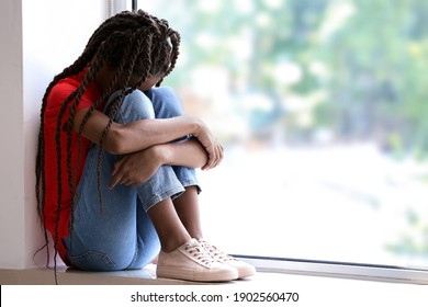 Sad African-American girl sitting on windowsill. Stop racism