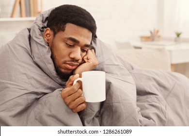 Sad african-american man with flu wrapped in warm blanket, holding cup with tea, copy space