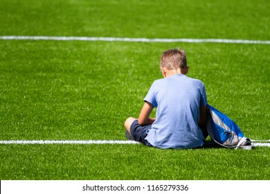 Sad alone boy with backpack sitting stadium outdoors