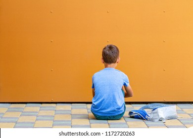 Sad alone boy sitting near colorful wall outdoors