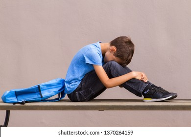 Sad alone child sitting on the bench outdoors