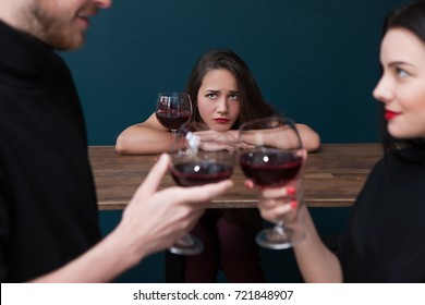 Sad alone female in bar. Jealousy backdrop. Love triangle, cheating relationships. Unhappy betrayed woman in focus on blue background, loneliness concept