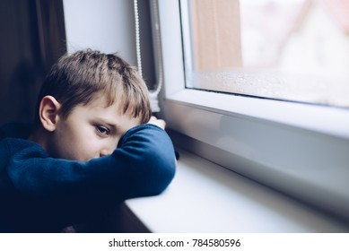 Sad alone little boy child looking through the window