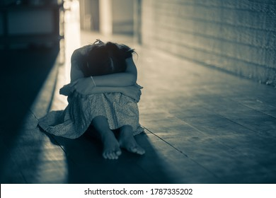 Sad alone little girl sitting at the door in the dark, Depression and anxiety disorder concept