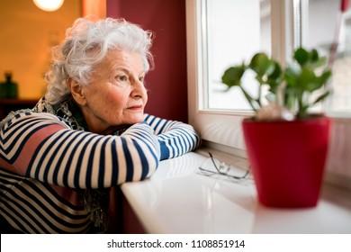 Triest alleen senior vrouw op zoek door raam thuis, eenzaamheid concept