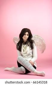 Sad angel sitting on the floor against pink background