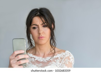 Sad and Angry Bride with Mobile Phone in the Hand