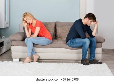 Sad Angry Cheating Couple Sitting Back To Back On Sofa At Home