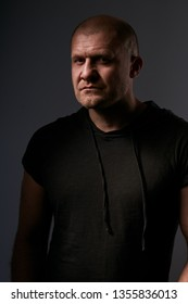 Sad angry crime man with bald head looking mystery and aggressive in black shirt on dark grey background. Closeup portrait