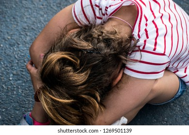 Sad and angry girl with the face sitting on the floor with her head on her lap. Psicological abuse is forbidden at schools, bullying and abusive behaviours.