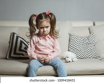 Sad or angry little girl, victim, holding toy dog