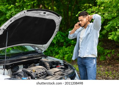 Sad arab man looking at car engine and calling to auto service, got broken at highway on a way to countryside. Middle-eastern guy having phone conversation with friends, asking for help with auto