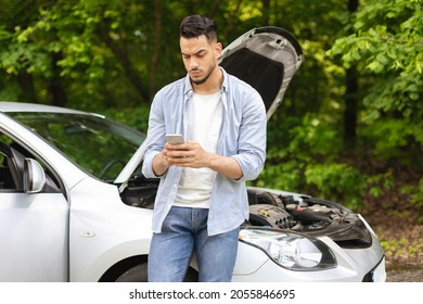 Sad arab man looking for nearest auto service, using smartphone, got broken at highway on a way to countryside. Middle-eastern guy chatting with friends, asking for help with auto